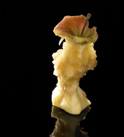 noyau: tourn� en studio d'un trognon de pomme � l'arri�re r�fl�chissant noir Banque d'images