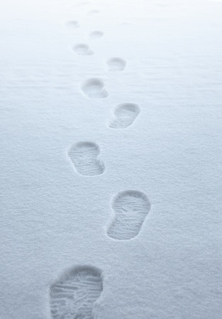 symbolic picture showing boot traces walking away in fresh fallen snow photo