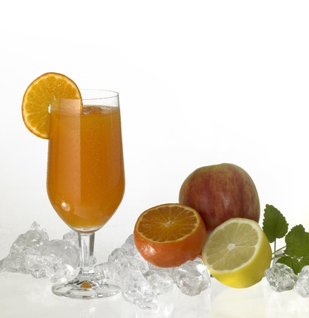 commercialization: studio photography showing a stemware glass filled with fruit juice, sliced orange and drinking straw. Itu00b4s located in orange background with some fruits and crushed ice