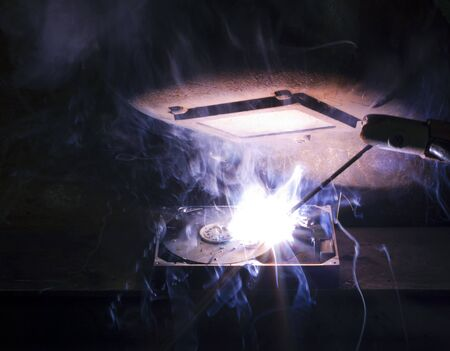 fixed disk: welding scenery with hard disk drive, welding mask detail and flashy light Stock Photo