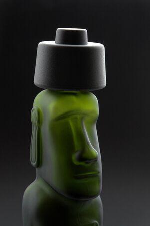 glaube: head of a moai-styled bottle in dark back