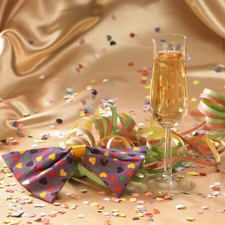 fluting: carnival background with filled champagne glass in floating satin back with streamers and confetti