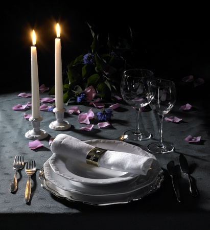 feastful place setting with floral deco and candlelight in dark back photo