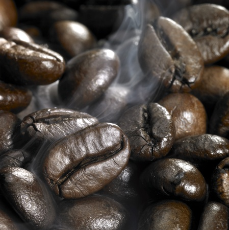 closeup photography of  roasted brown coffee beans and smoke photo