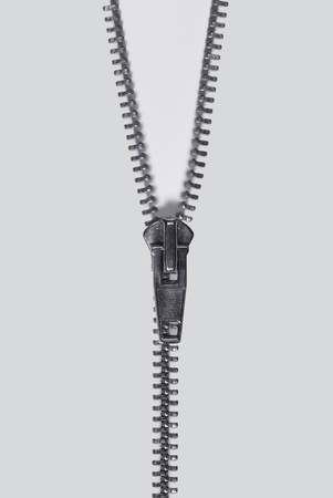 reachability: studio photography of a long zipper half closed, in light back