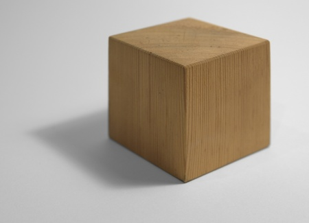 midsagittal: studio photography of a light brown wooden cube isolated on white with shadow