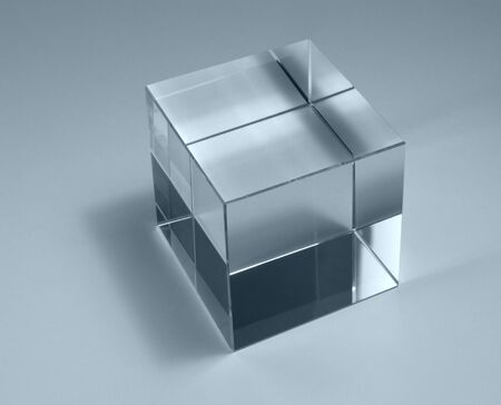 physics theme with studio photography of a solid glass cube in light back, blue toned
