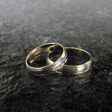 accouterment: studio photography of two golden wedding rings on each other with black glossy stone surface Stock Photo