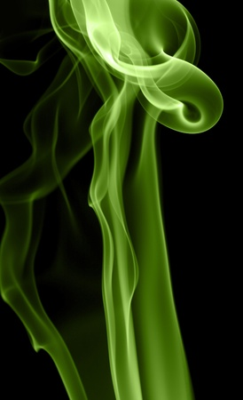 wavily: abstract picture showing some vibrant yellow and green colored smoke in black back Stock Photo