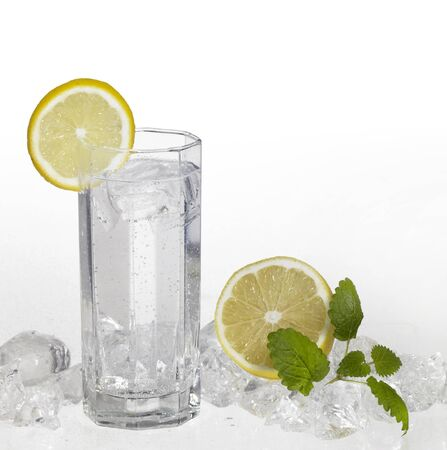 studio photography of a clear soft drink in light back with lemon and ice cubes photo