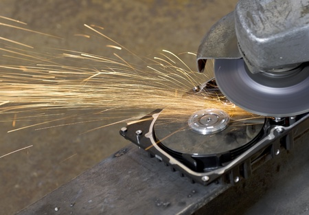 data recovery: hard disk drive with rotating grinder and sparks in front of rusty back