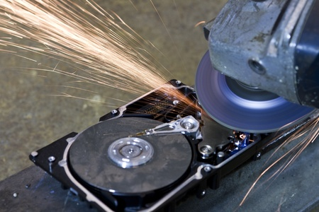 fixed disk: hard disk drive with rotating grinder and sparks in front of rusty back