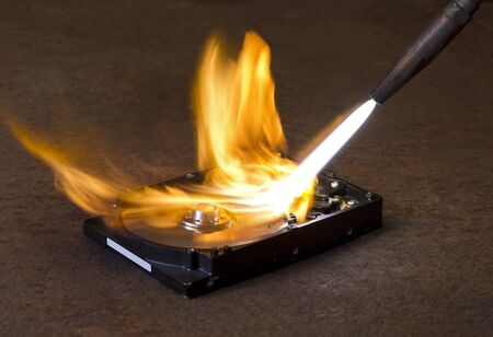 fixed disk: symbolic technology theme showing a welding torch tip and dashing flame burning a fixed hard disk wich is located on rusty metallic ground Stock Photo