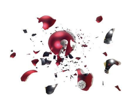 allegory painting: studio photography of a broken red christmas tree ball with lots of shards on the ground in white back Stock Photo