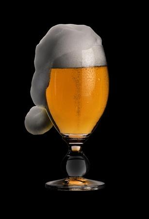 moistness: studio fotografico che mostra un bicchiere di birra pils con schiuma divertente a forma di tappo di gelatina in borsa posteriore nero