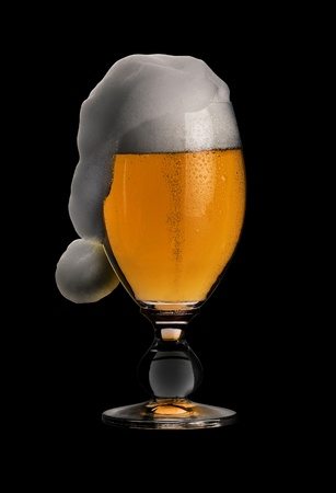 studio photography showing a glass of pils beer with funny foam shaped like a jelly bag cap in black back