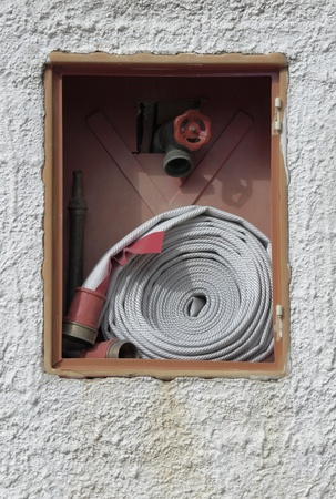 public firefight equipment with hose and faucet in a plastered wall photo
