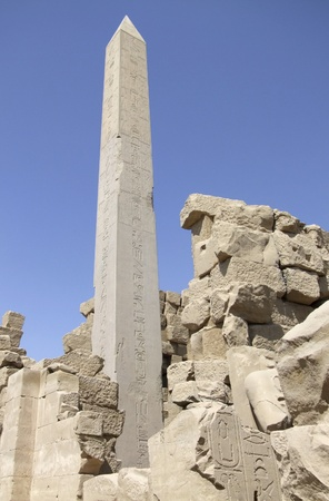 obelisk stone: scenery around Precinct of Amun-Re in Egypt showing a historic obelisk and stone remains in front of blue sky