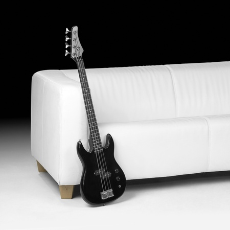 black bass guitar lean against white couch in dark back photo