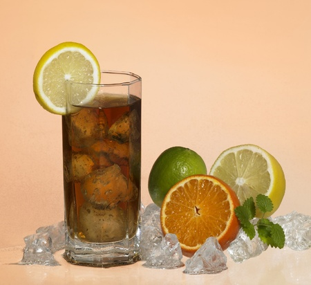 studio photography of a drinking glass filled with brown lemonade and ice cubes, located in orange background with citrus fruits and ice cubes photo
