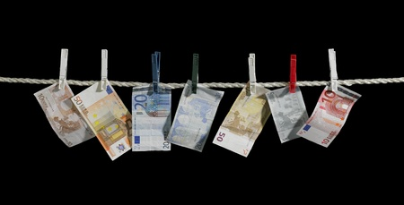 meltdown: clothesline with some euro banknotes fixed with clothes pins in black back