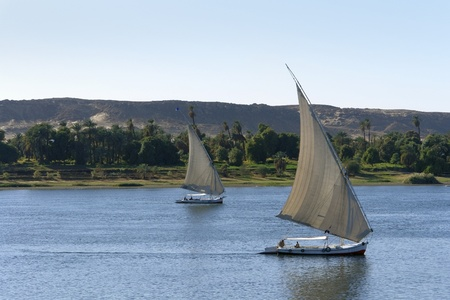 waterside River Nile scenery including two sailing ships between Aswan and Luxor in Egypt (Africa)