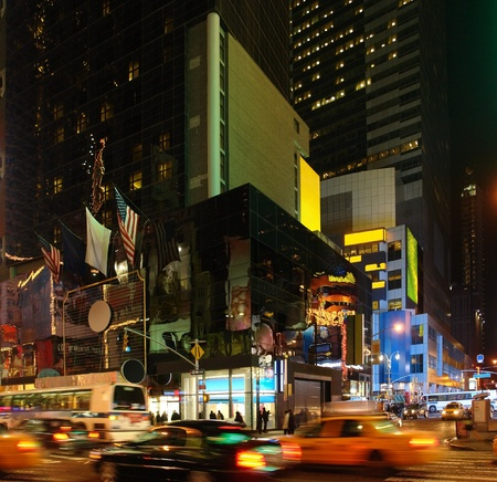 new york night: vivid night scenery showing the fantastic illuminated Times Square in New York (USA) with driving cars Editorial