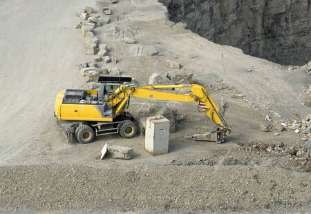 degradation: yellow stone pit digger in quarry ambiance