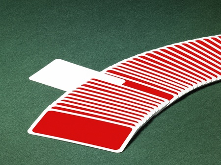 studio photography of spread out playing cards in a row with one chosen, located on green felt background photo
