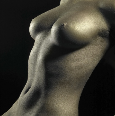 studio photography of a naked female body detail bodypainted with golden color in black back