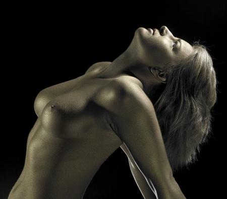 mujer desnuda: estudio de fotograf�a de un detalle chica dorada bodypainted en fondo negro Foto de archivo