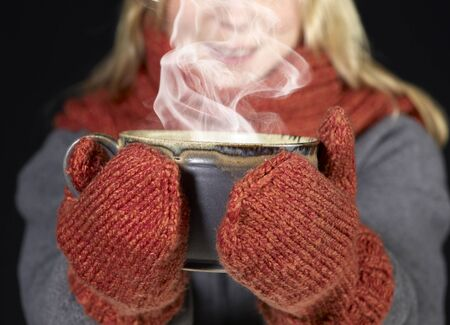 detail of a woman with woolen gloves holding a hot steaming cup photo
