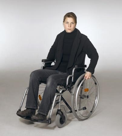 paraplegico: estudio de fotografía de una joven mujer sentada en una silla de ruedas en la parte trasera de color gris claro Foto de archivo