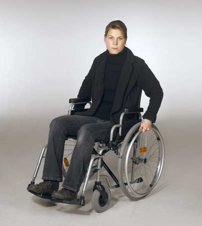 studio photography of a young woman sitting in a wheelchair in light grey back photo