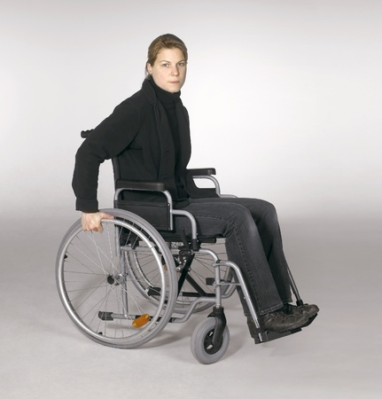 studio shot of a young woman in a wheelchair in light grey back Standard-Bild