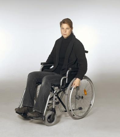 paraplegico: foto de estudio de una mujer joven en una silla de ruedas en color gris claro de nuevo Foto de archivo