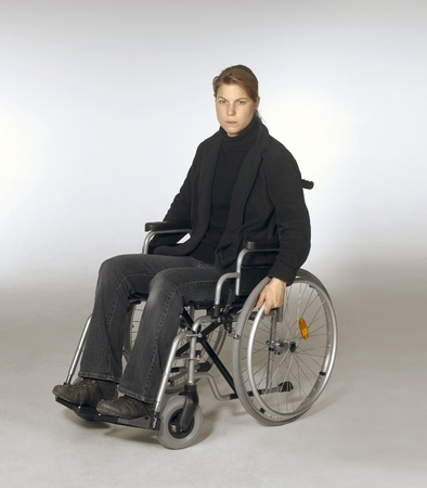 paraplegic: studio shot of a young woman in a wheelchair in light grey back Stock Photo