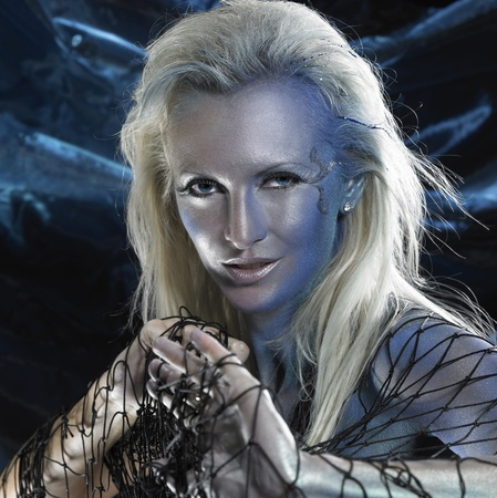 mystic mermaid theme showing the portrait of a bodypainted woman with black fishing net, studio photography in black back photo