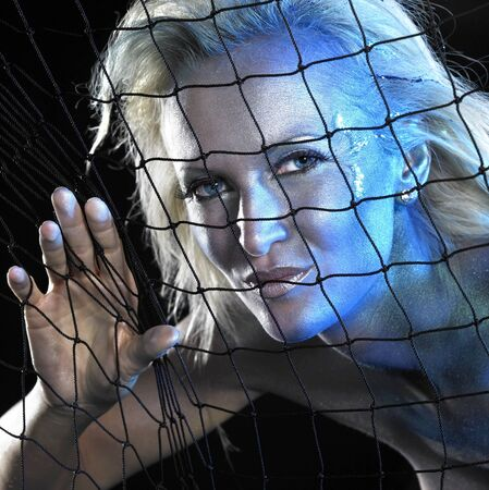 mystic mermaid theme showing a bodypainted woman portrait behind a fishing net, studio photography in black back photo