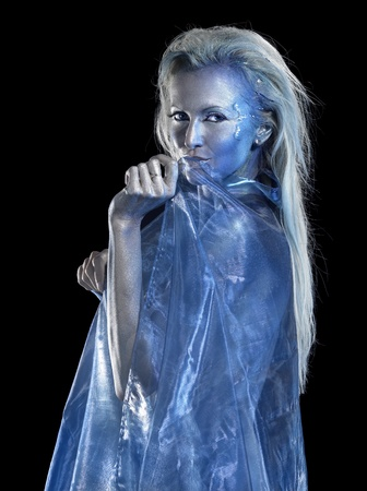 mystic mermaid theme showing a blond bodypainted woman coated with translucent blue fabrics, studio photography in black back photo