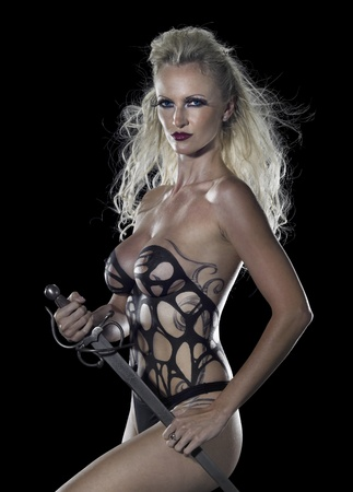 a bodypainted blond woman in dominatrix style while holding a sword in her hands, studio photography in dark back photo