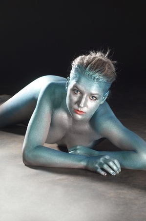 nude little girls: studio photography of a metallic bodypainted girl in dark back