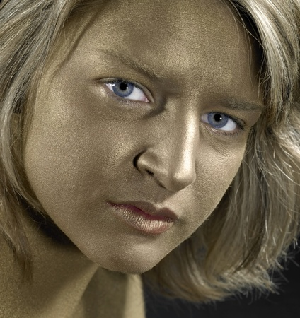 reachability: portrait with a golden bodypainted face of a young woman with blue eyes