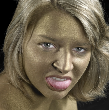 portrait of a angry young woman with golden bodypainted face