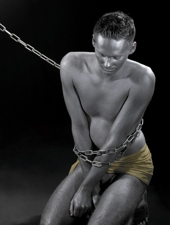 studio photography of a silver bodypainted man in chains sitting on the ground photo