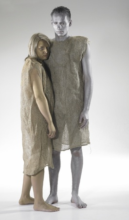 abject: bodypainted young man and woman dressed in gunnysacks. Studio shot in light grey back Stock Photo
