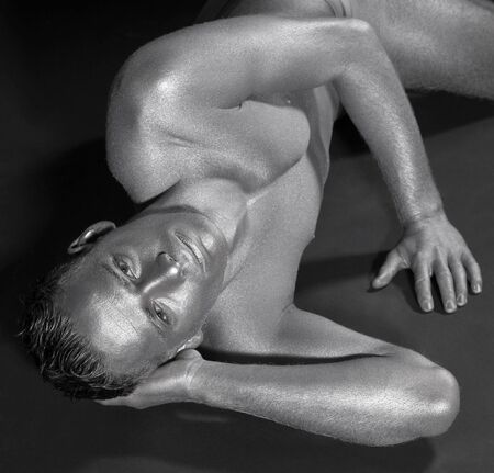 studio photography of a silver bodypainted man while resting on dark ground Stock Photo - 11402883