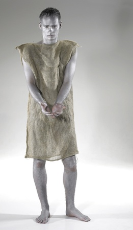 abject: begging poor young man dressed in a gunnysack, Studio shot in grey back