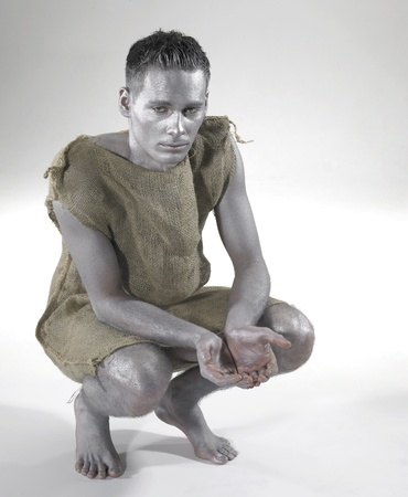 begging poor man dressed in a gunnysack. Studio photography in light back Stock Photo - 11402880