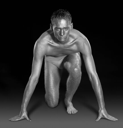 studio photography of a silver bodypainted young man ready to run Stock Photo - 11402881